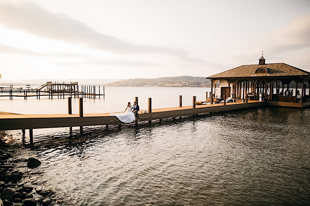 A bride and groom sit on a dock on a lake at sunset.