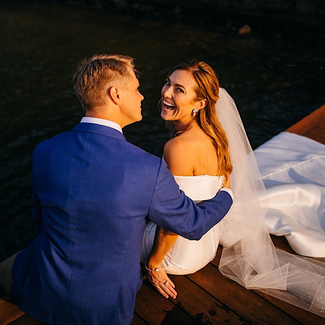 A groom embraces his bride while she laughs. They both sit on the edge of a dock.