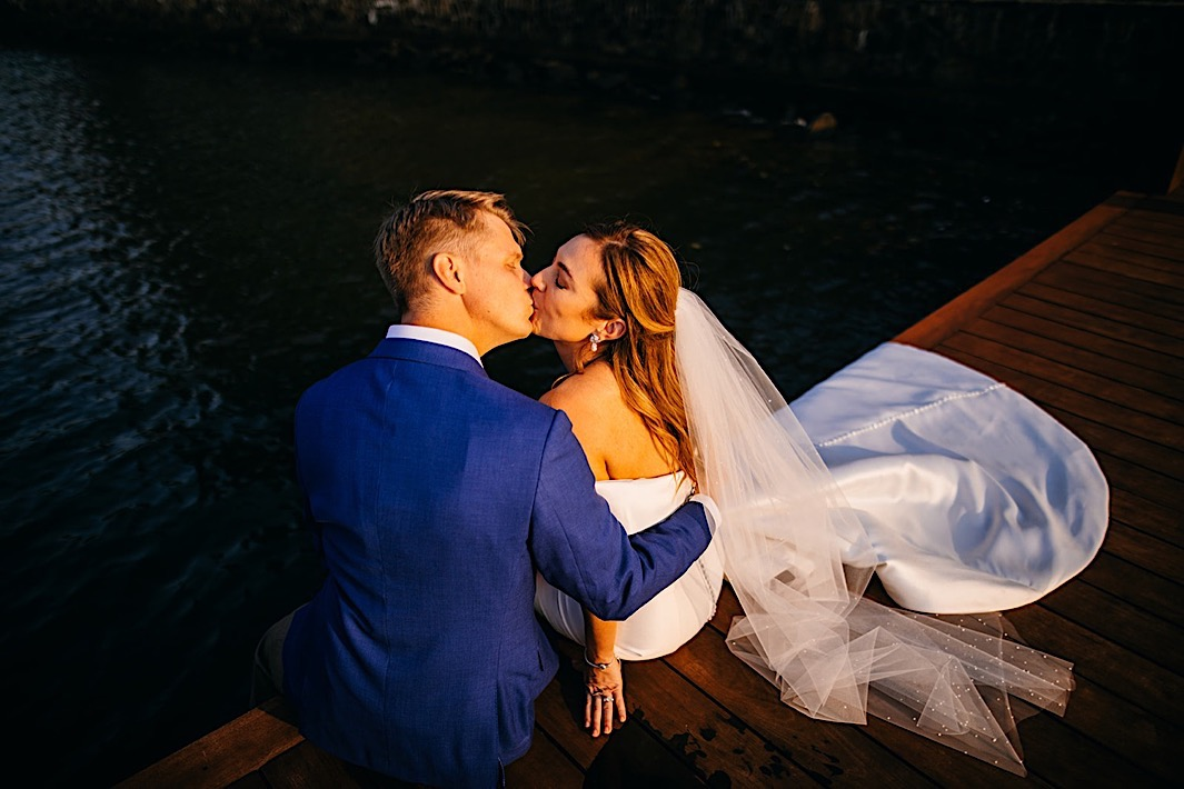 A bride and groom sit on the edge of a dock and kiss.