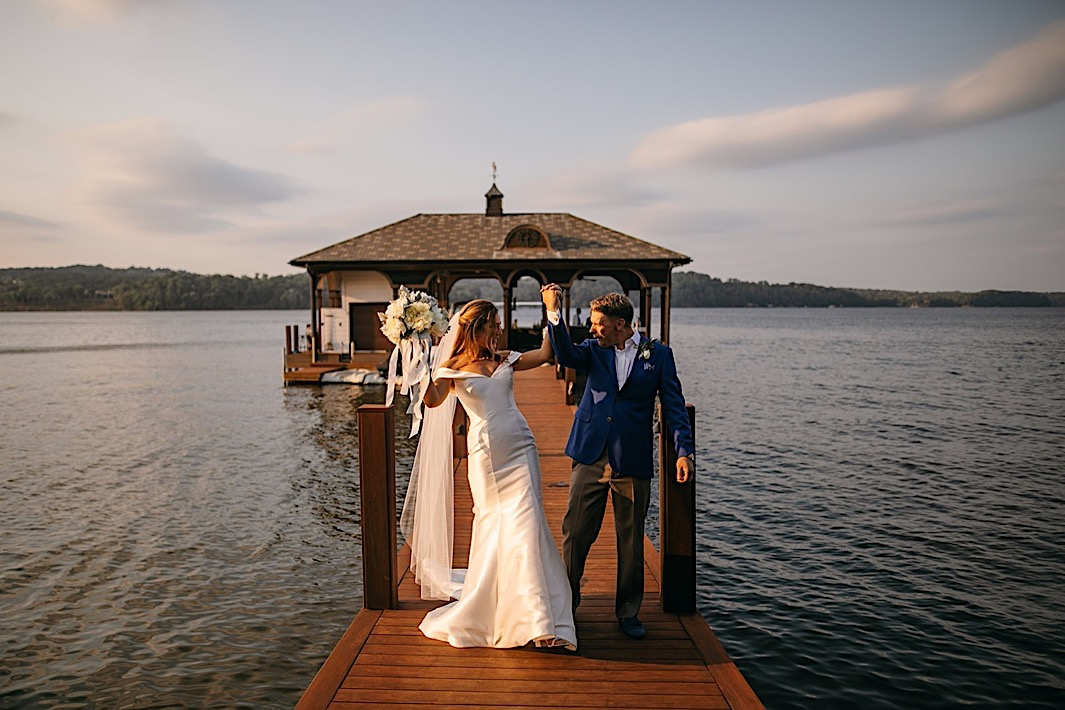 A bride and groom raise their interlocked hands on a dock on a lake.