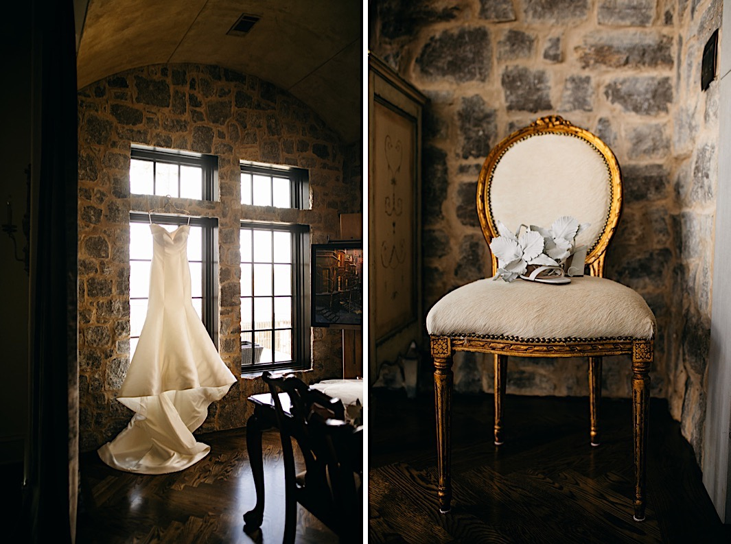 A wedding dress hung in a stone window and a pair of light blue shoes displayed on a cream and gold chair.