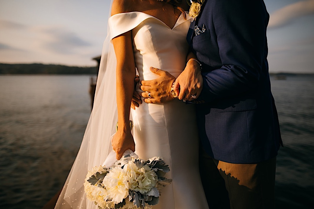 A bride and groom embrace on a dock on a lake at sunset.