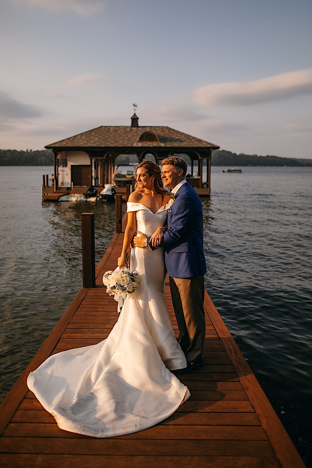 A bride and groom embrace and admire the sunset on a dock on a lake.