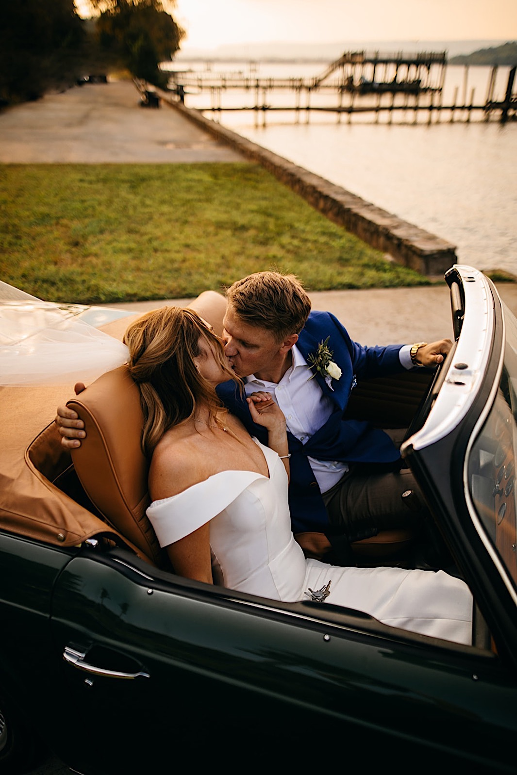 A bride and groom kiss in the front seat of a vintage car.