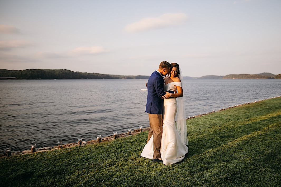 A bride and groom embrace on a stretch of lawn next to a lake.
