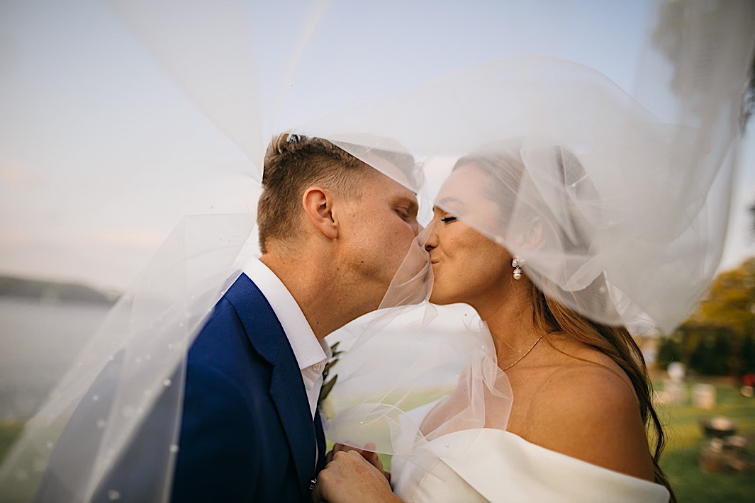 A bride and groom kiss through the bride's veil in front of a lake.