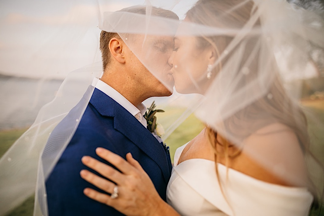 A bride and groom kiss beneath the bride's veil in front of a lake.
