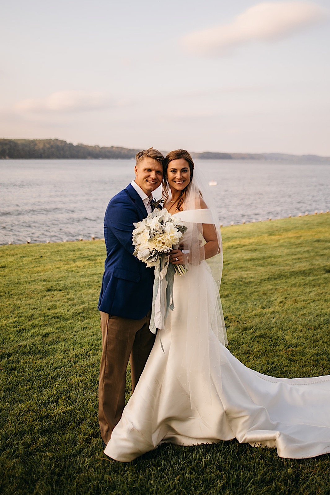A bride and groom embrace and smile for a photo on a lawn in front of a lake.