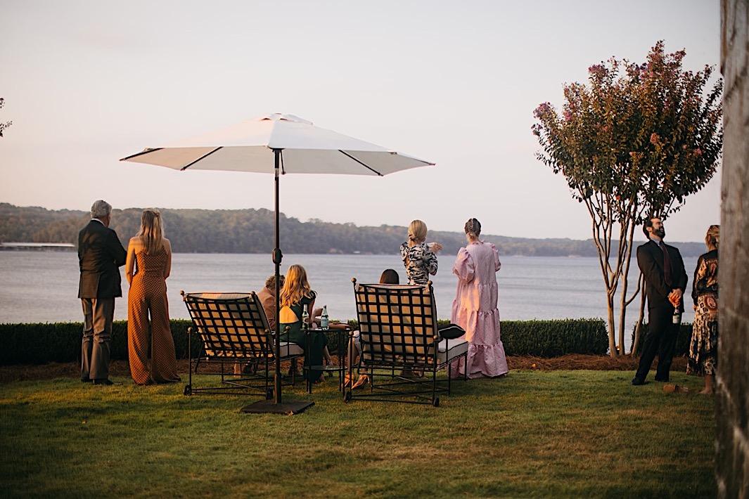 Wedding guests admire the lake view at a big backyard wedding.