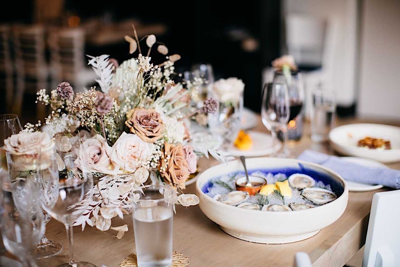 A table set a bowl of oysters on ice with a pink and white dried floral arrangement by Fox & Fern Botanical Design.