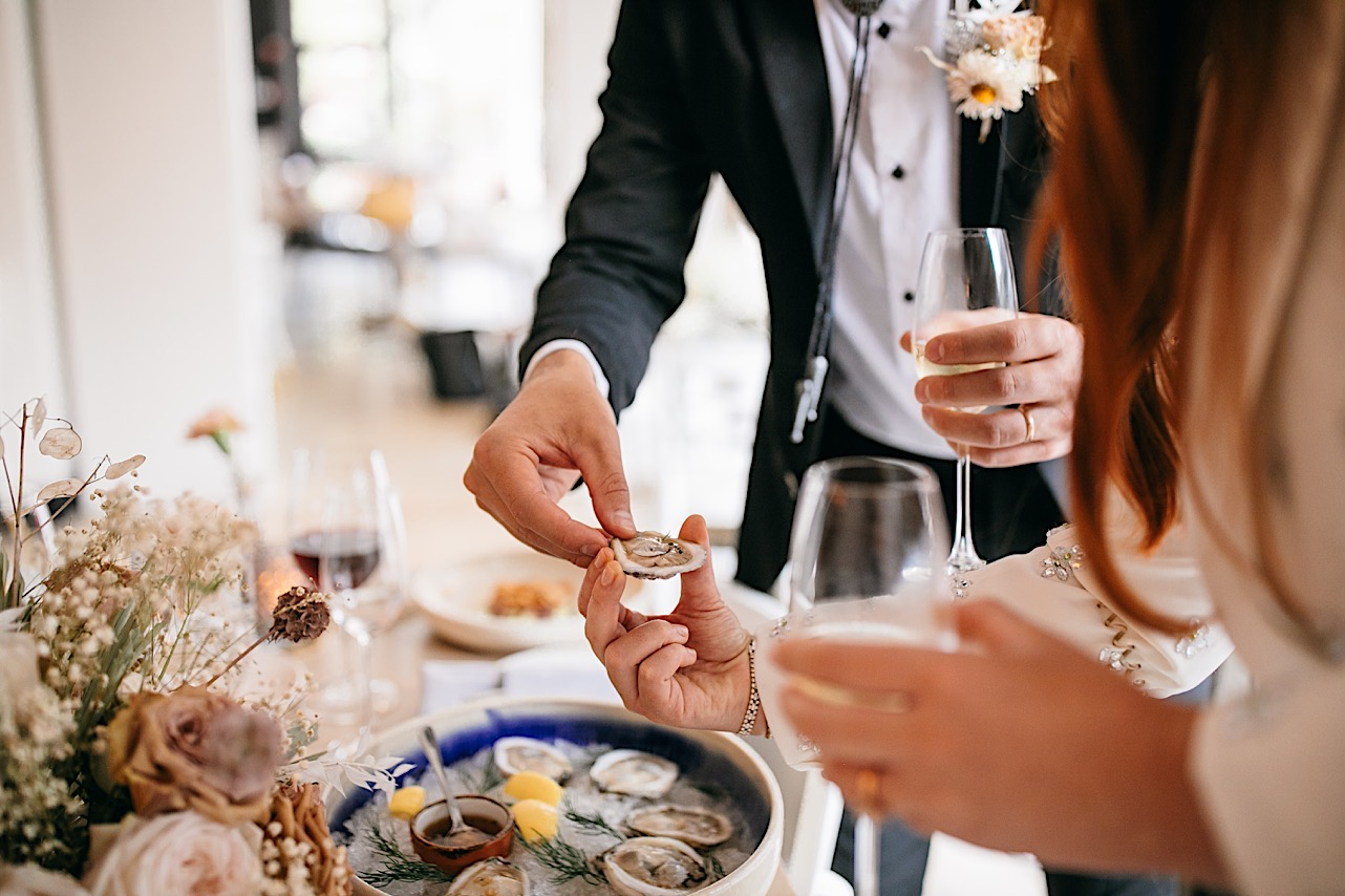 A groom hands his bride an oyster on a half shell at Easy Bistro & Bar.