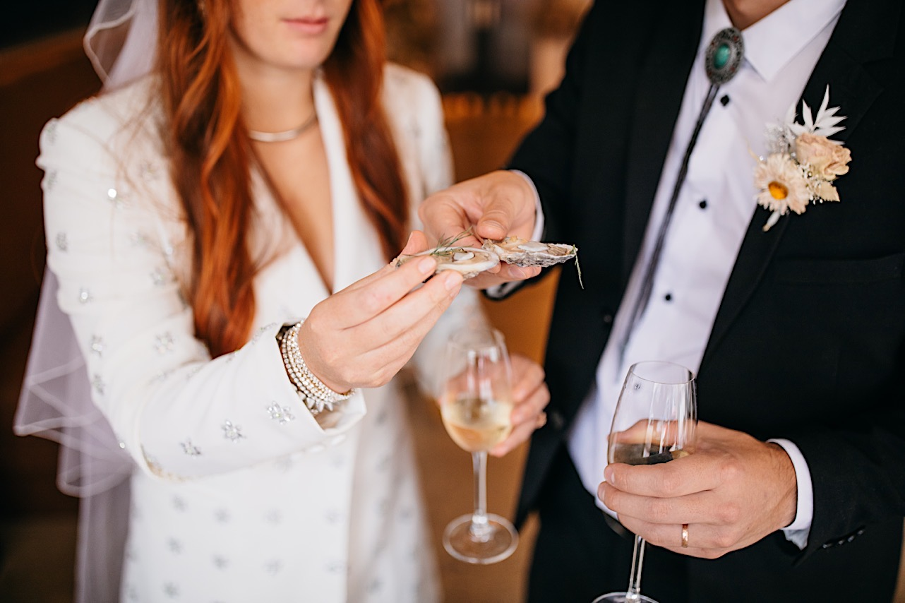 A bride and groom cheers with oysters on a half shell.