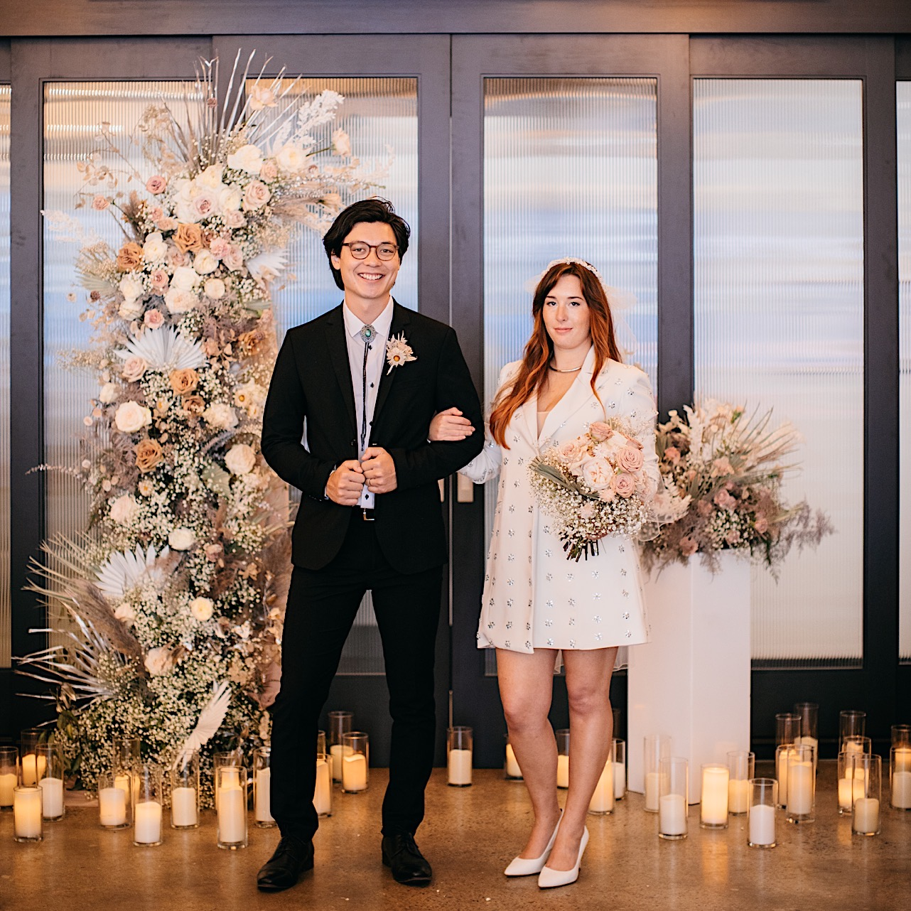A bridge and groom stand in front of a pink and white floral arrangement and scattered candles at Easy Bistro & Bar.