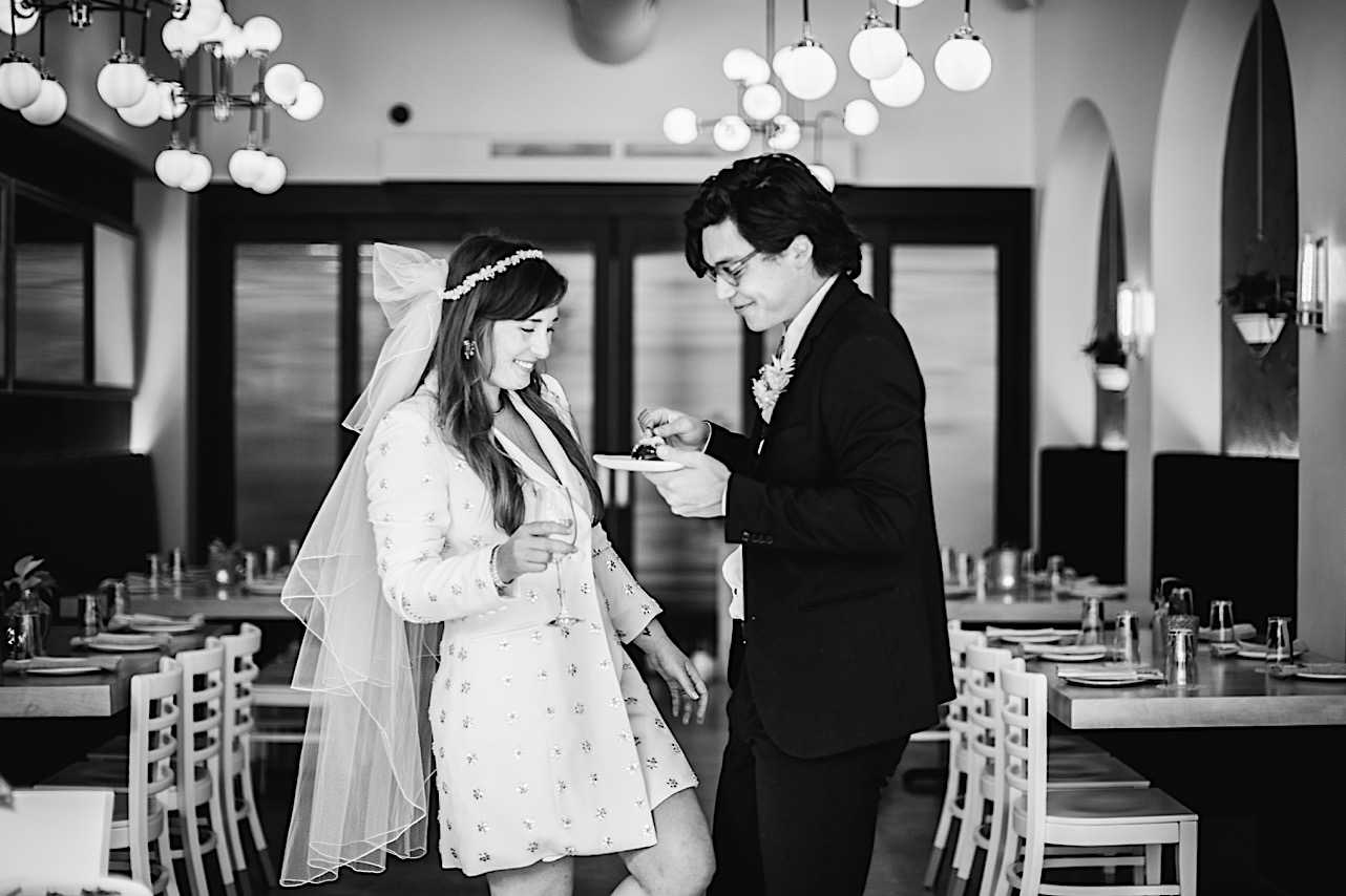 A black and white shot of a bride and groom sharing a chocolate dessert.