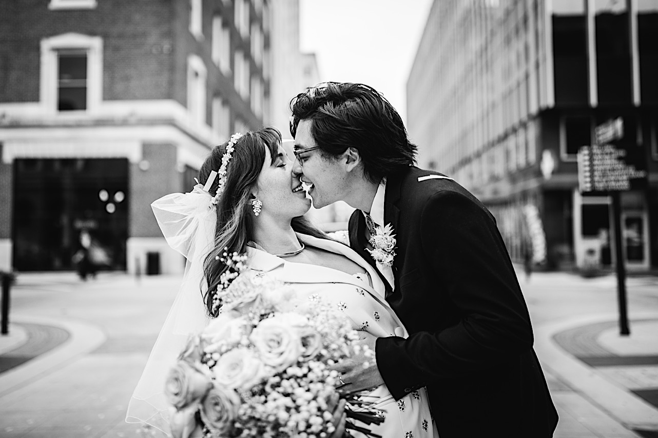A black and white shot of a bride and groom kissing in downtown Chattanooga.