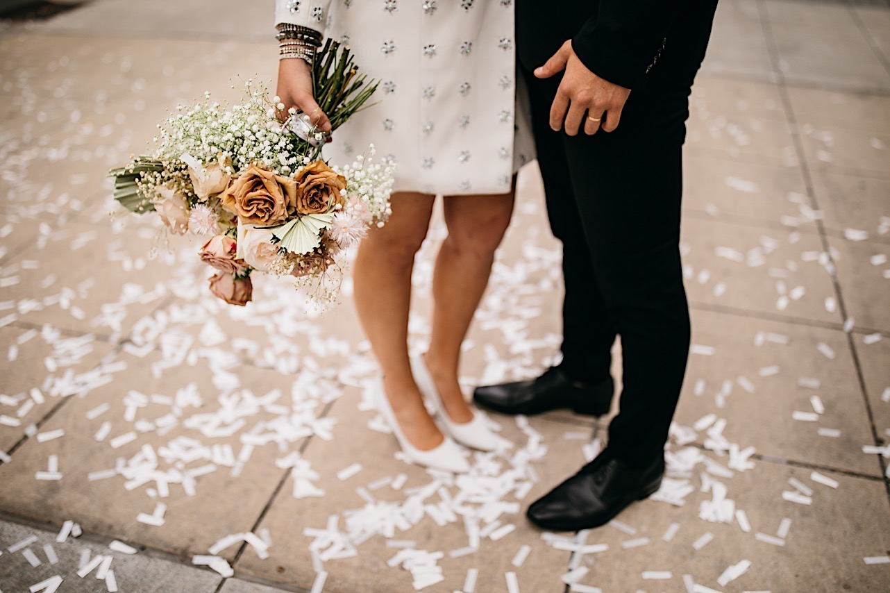 A bride and groom stand on scattered confetti in downtown Chattanooga.