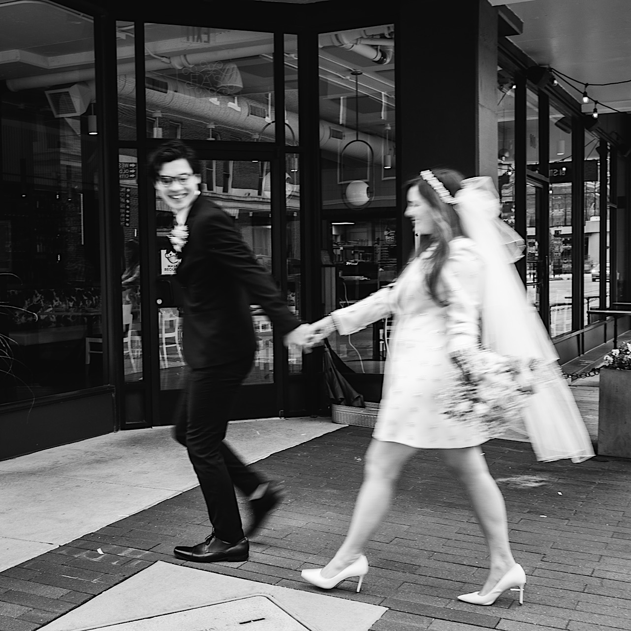 A black and white shot of a bride and groom walking through downtown Chattanooga.