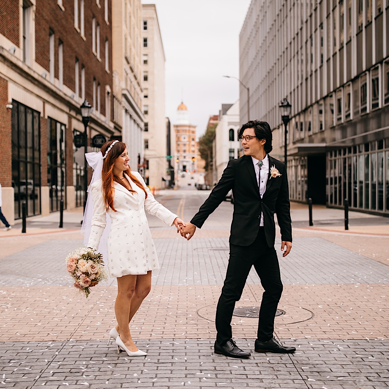 A bride and groom stand holding hands and smiling at each other in a downtown street.