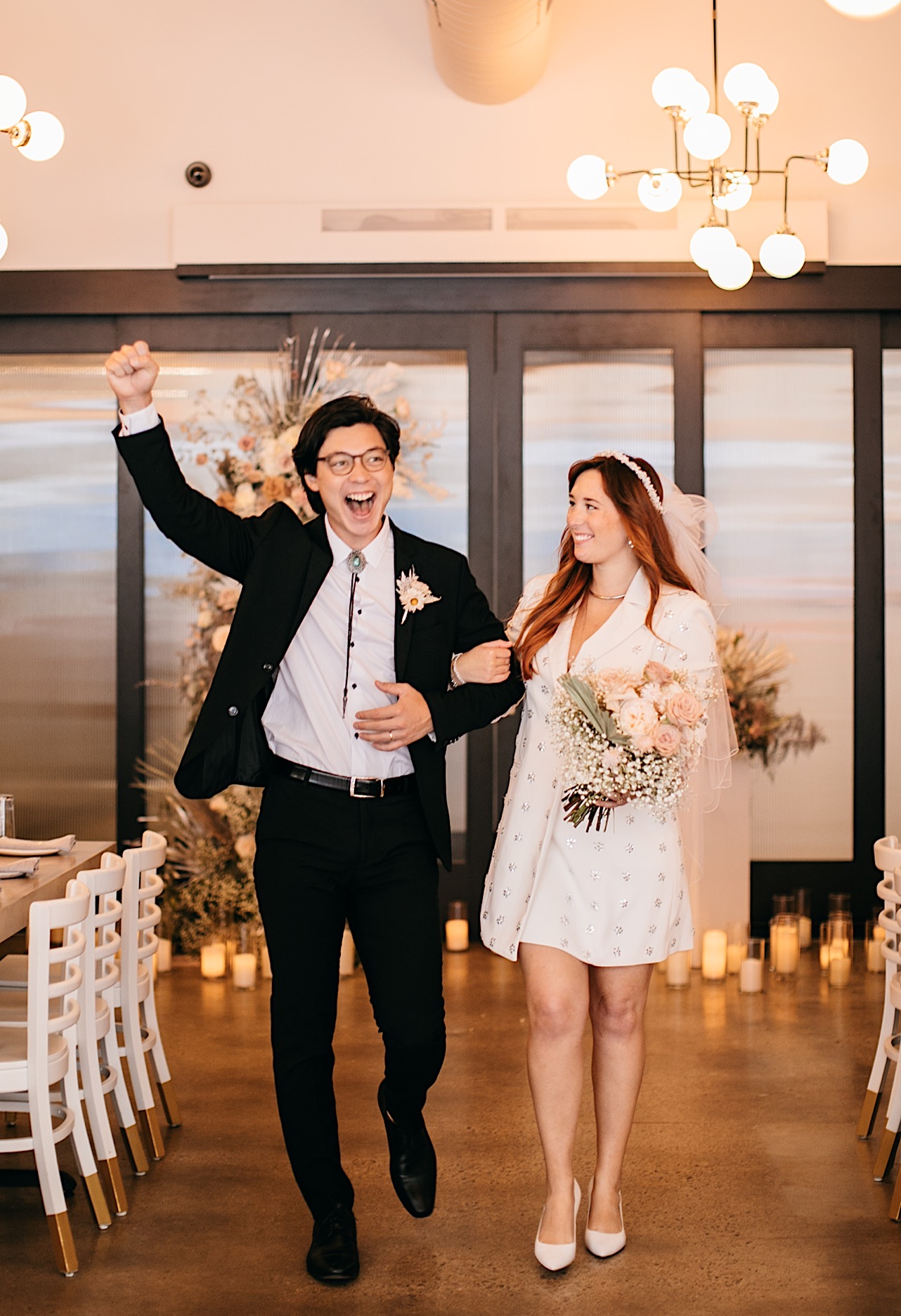 A groom holds his fist in the air as he and the bride walk down the aisle following their wedding ceremony.