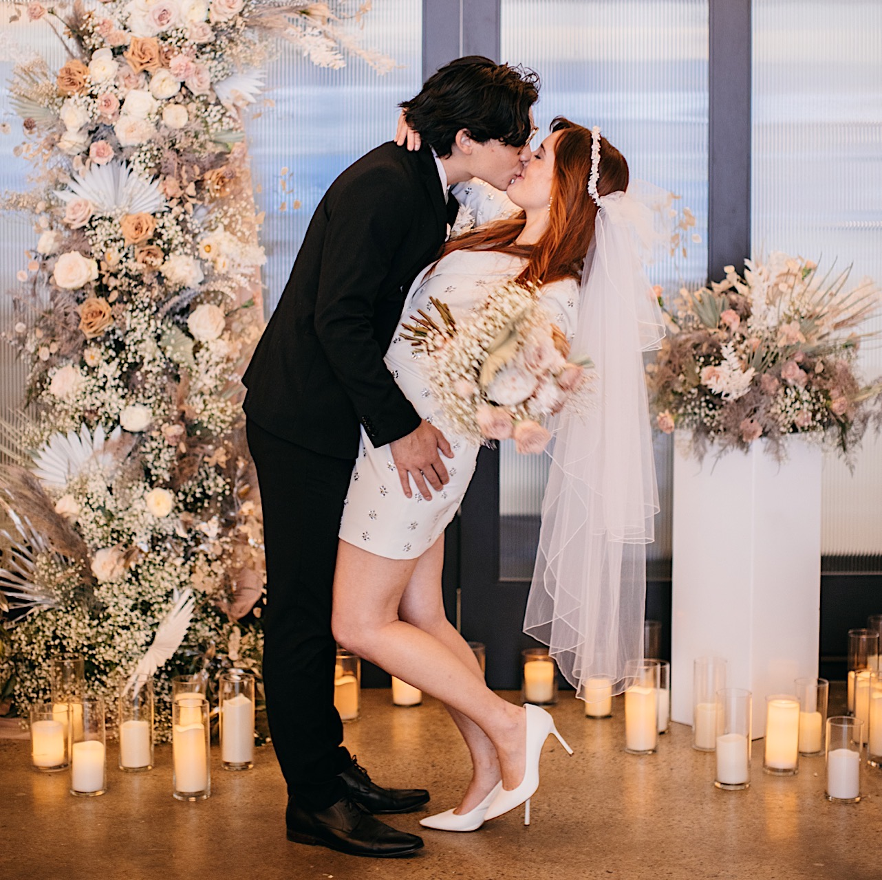 A groom kisses his wife in front of a floral arrangement and scattered candles.