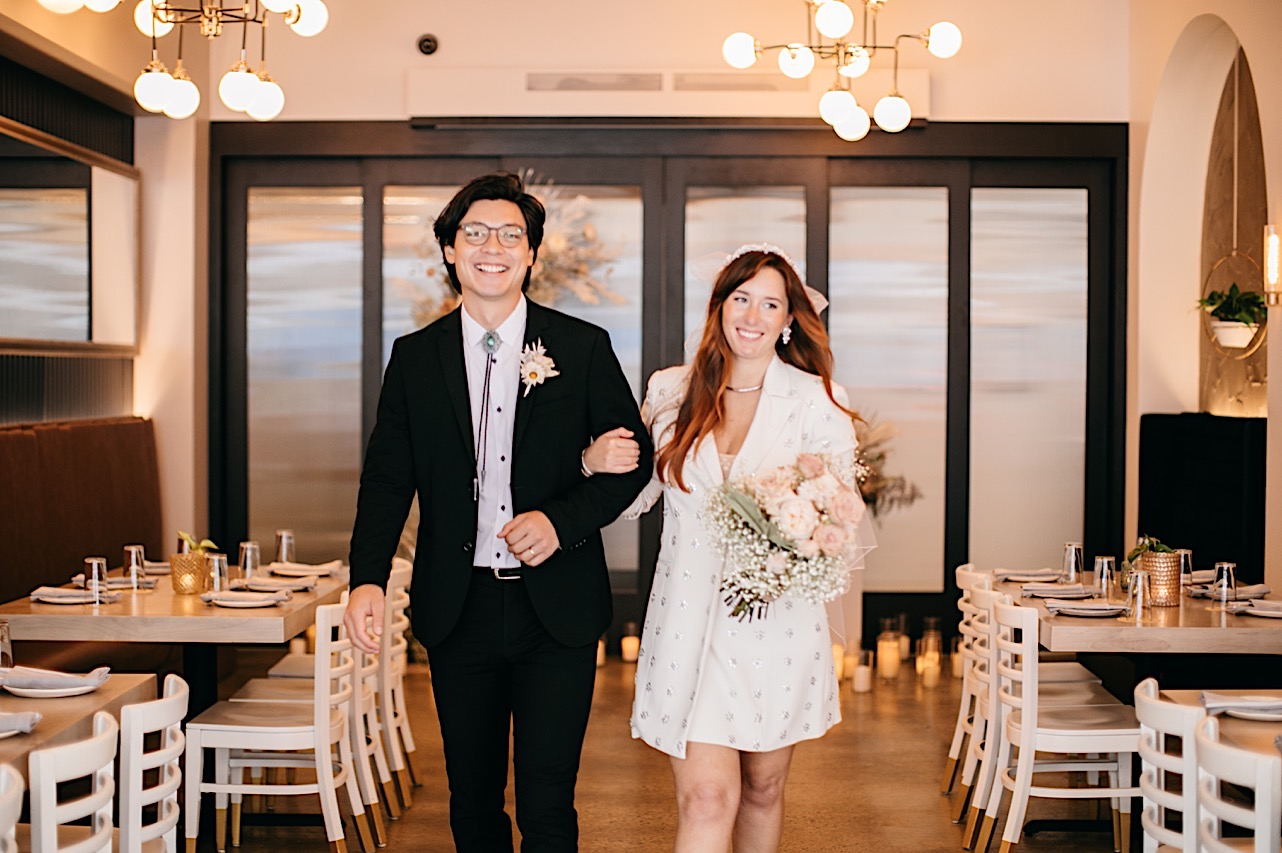 A bride and groom smile as they walk back down the aisle following their ceremony at Easy Bistro & Bar in Chattanooga.