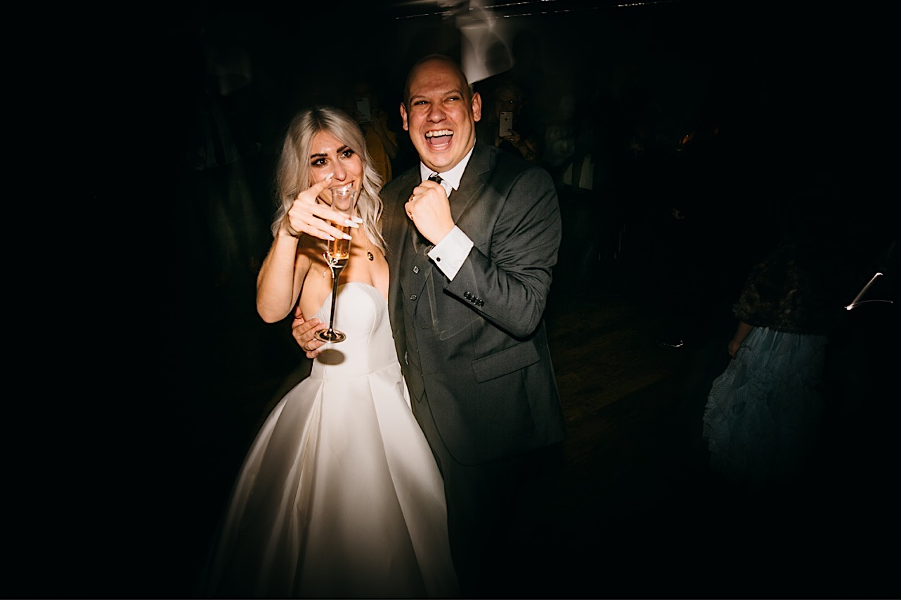 bride and groom hold each other on the dance floor and pose for a photo