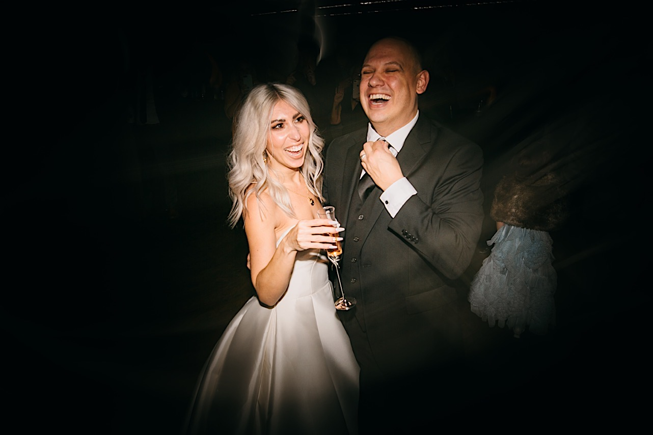bride and groom share a laugh on the dance floor