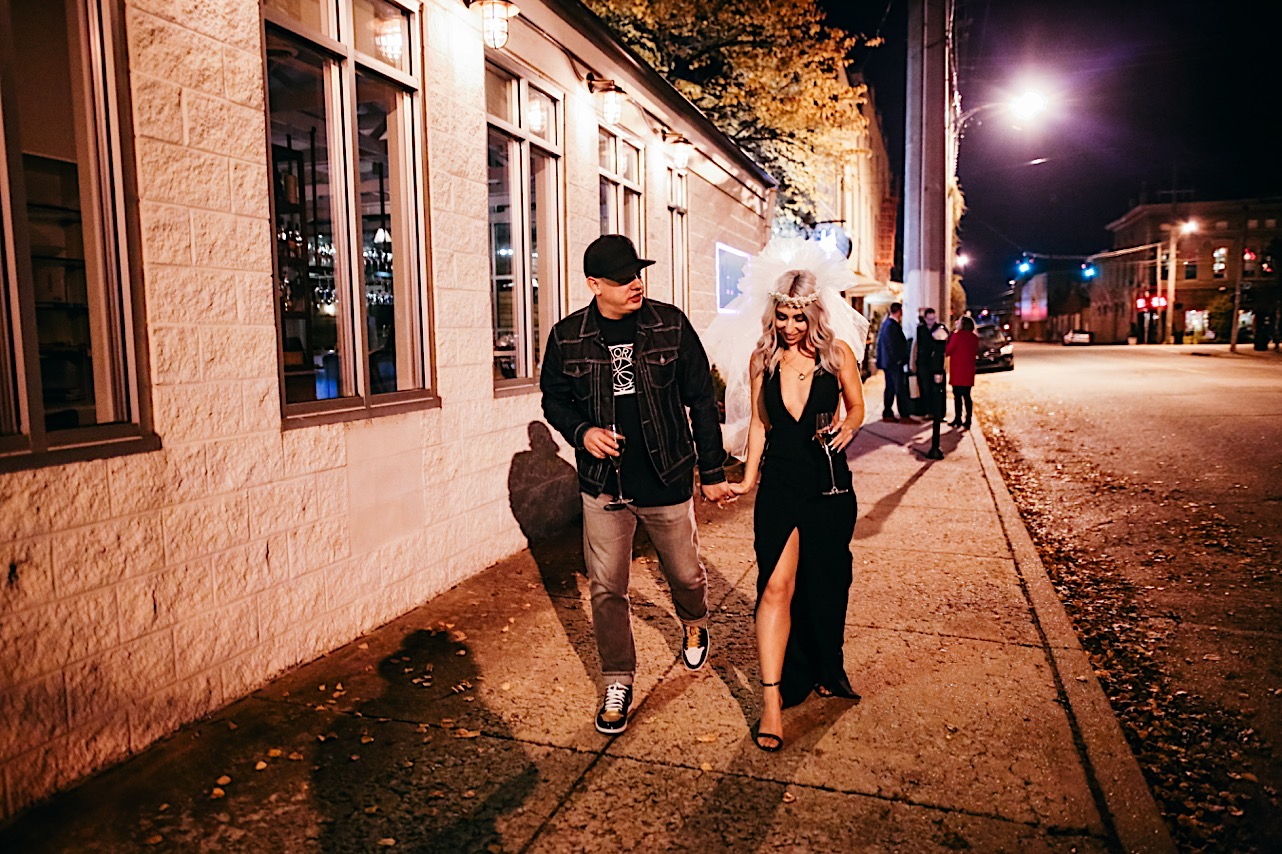 bride and groom drink champange as they walk down the side walk at their halloween elopement
