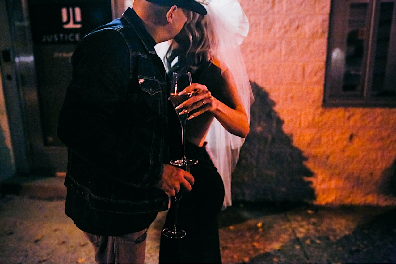 bride and groom share a kiss on the sidewalk at their halloween elopement