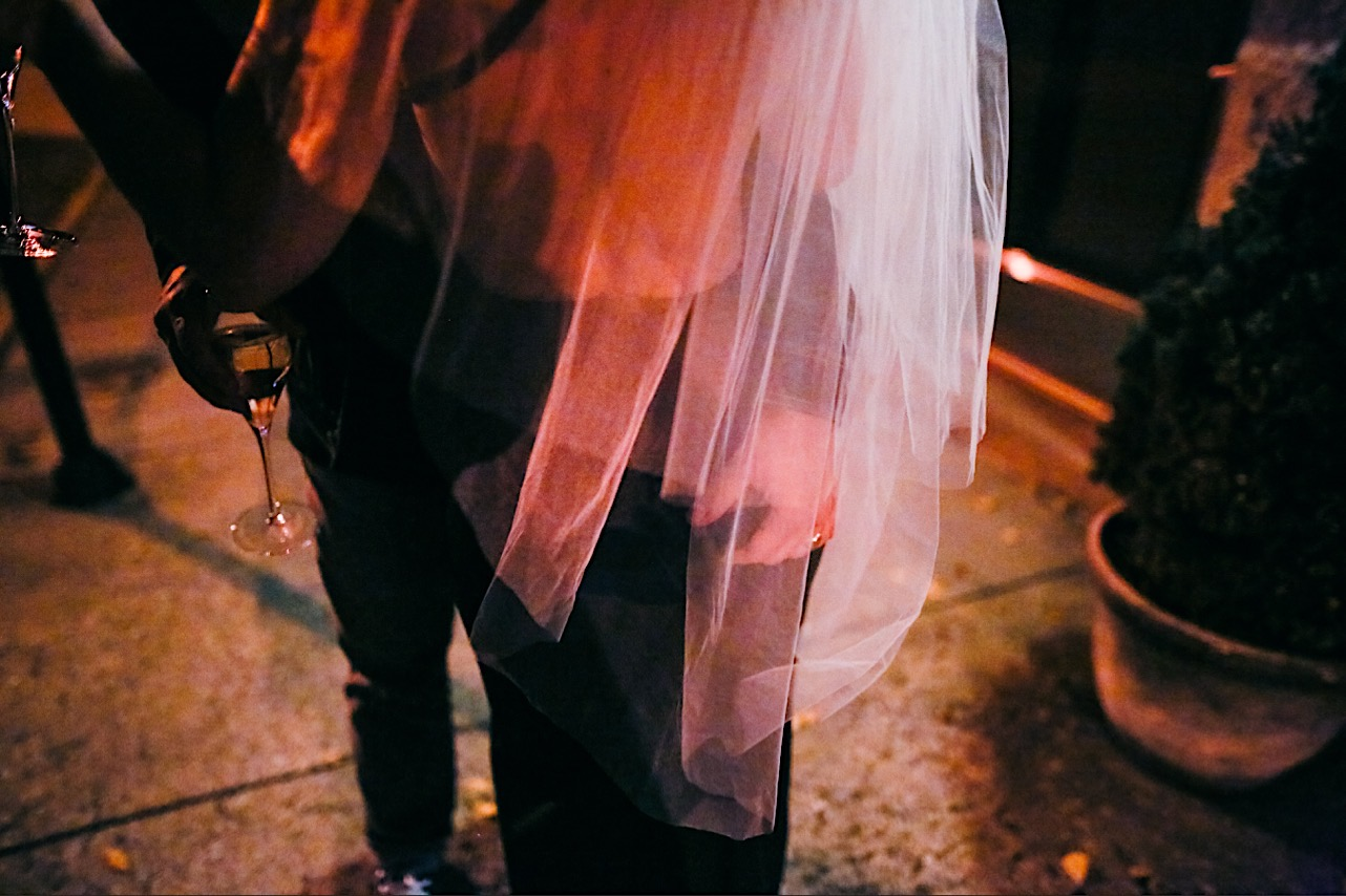bride shows her veil outside at her halloween elopement