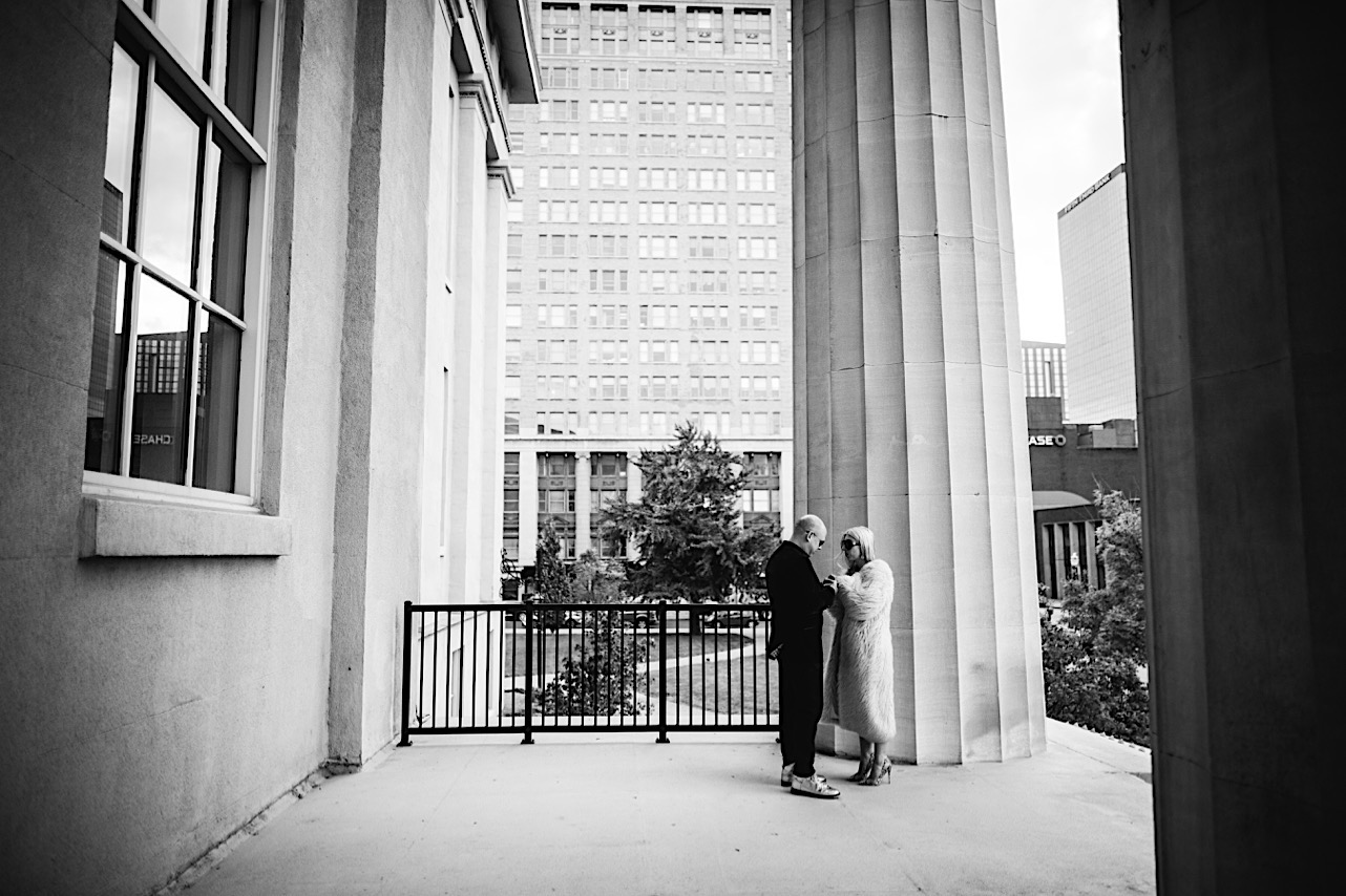 a black and white photo of a halloween elopement at the courthouse where the groom is holding the brides hand