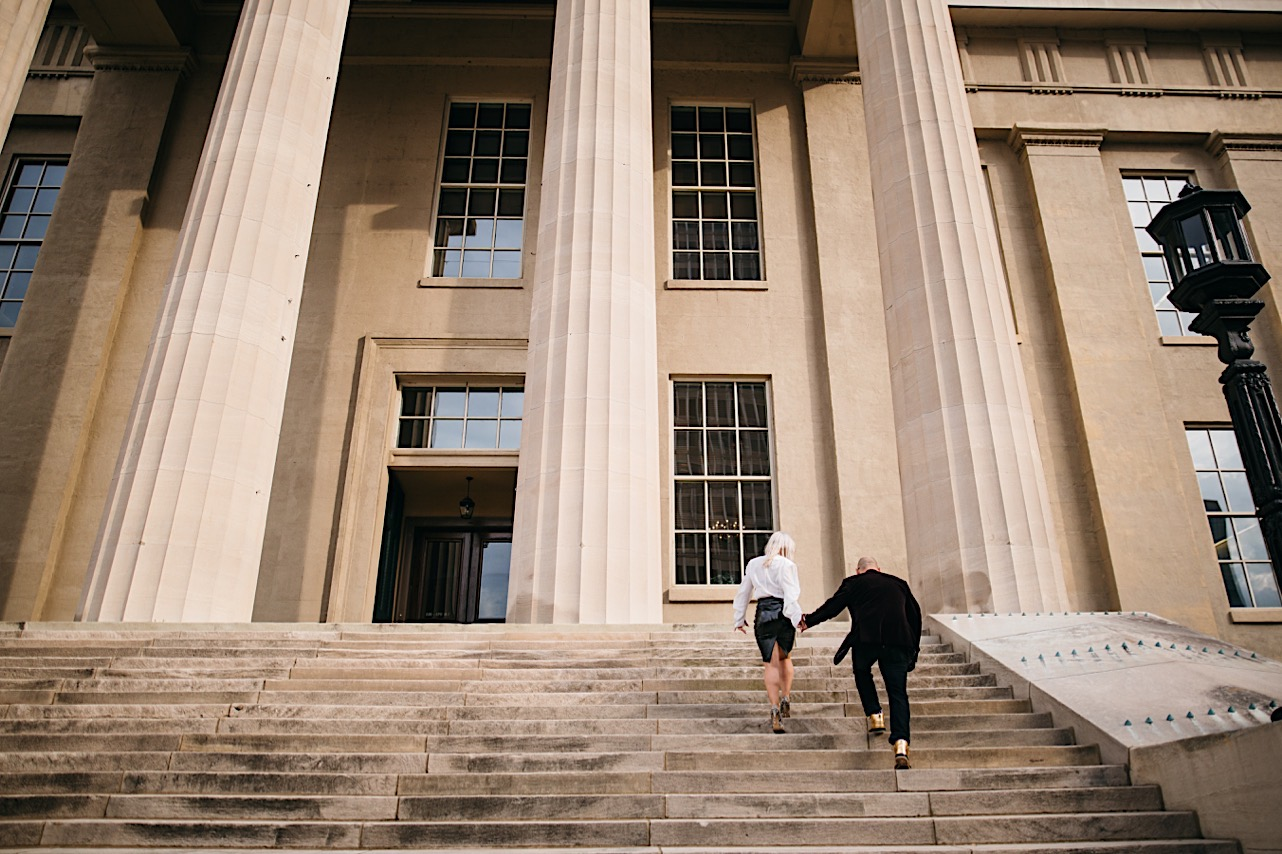 bride is walking up the stairs of the courthouse ahead of the groom while holding his hand at their halloween elopement