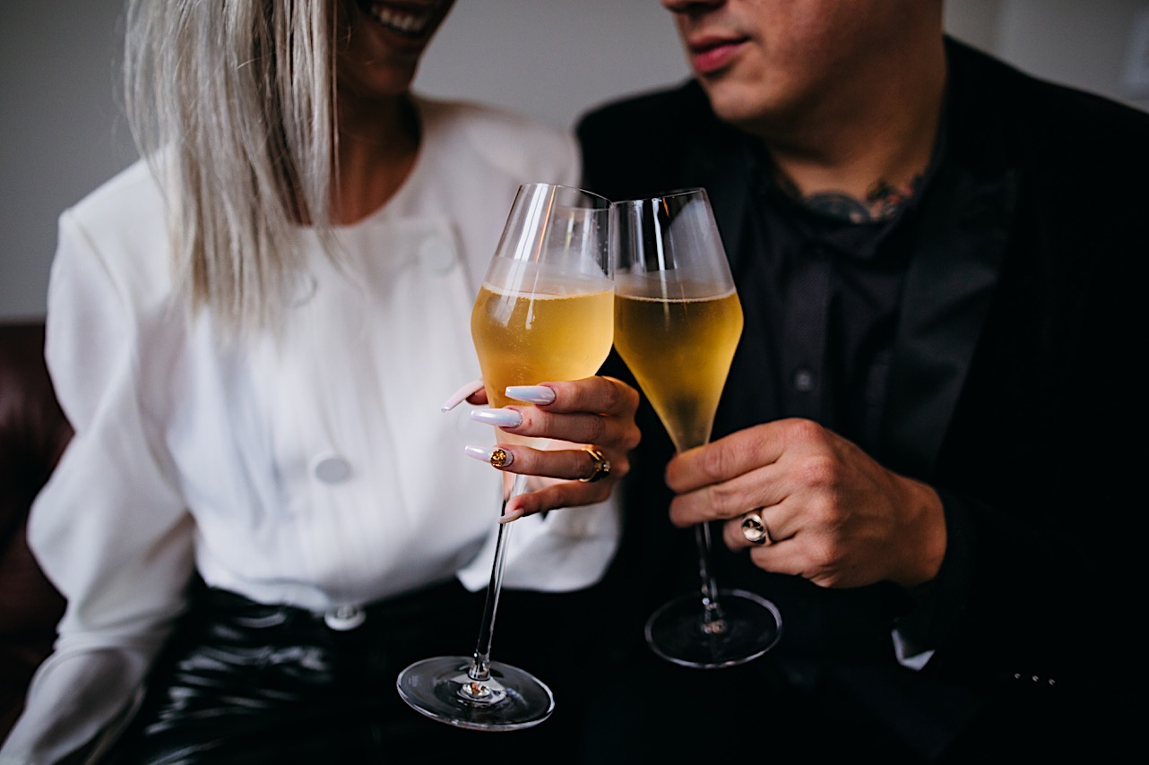 bride and groom sit on the couch at the courthouse and toast with champange at their halloween elopement