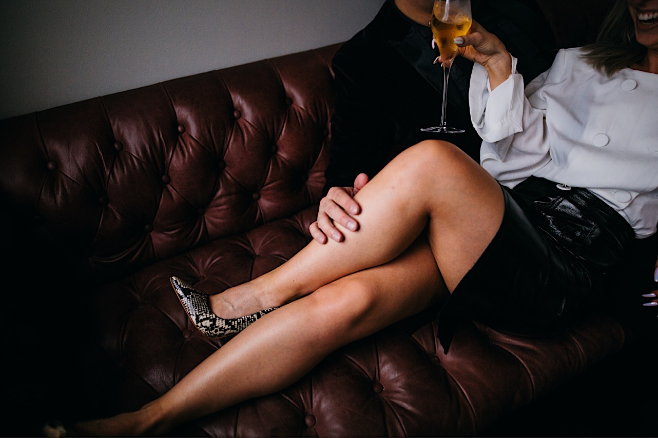 groom rubs brides leg as she drinks her champange on the couch at the courthouse during their halloween elopement