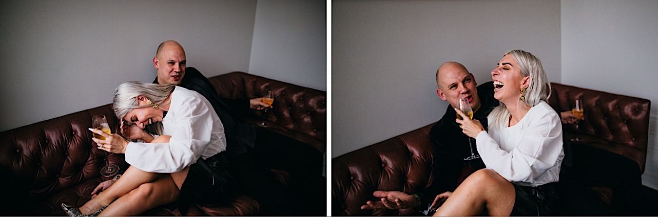 bride and groom share a laugh on the couch at their halloween elopement
