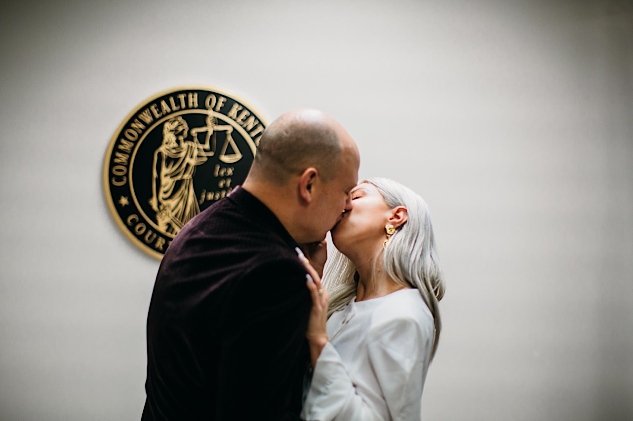 bride and groom in casual clothes share a kiss at their courthouse halloween elopement