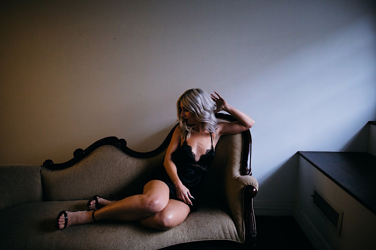 bride sits on couch in her black slip and heels as she gets ready for her halloween elopement