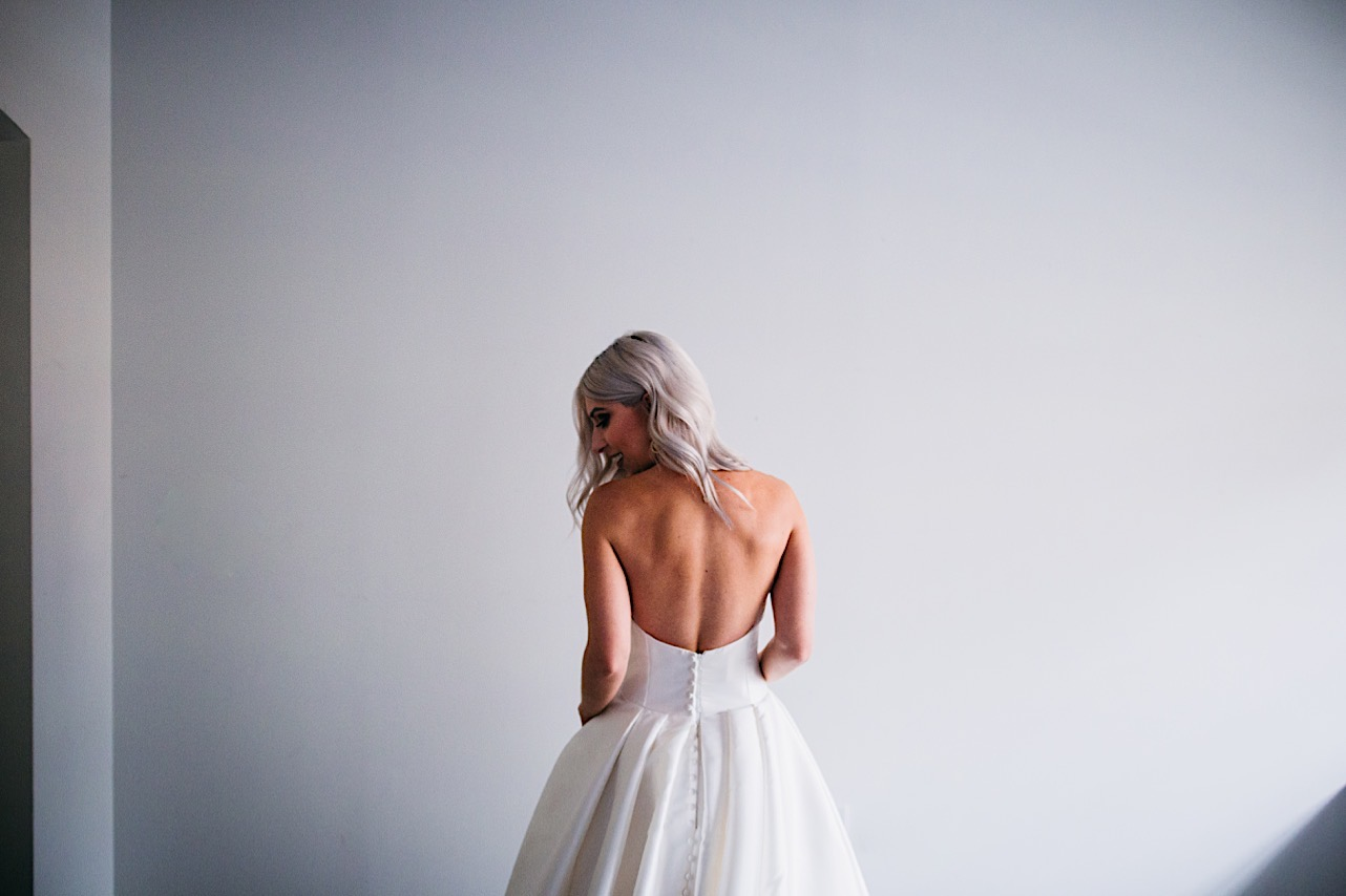 bride shows the back of her wedding dress at her halloween elopement