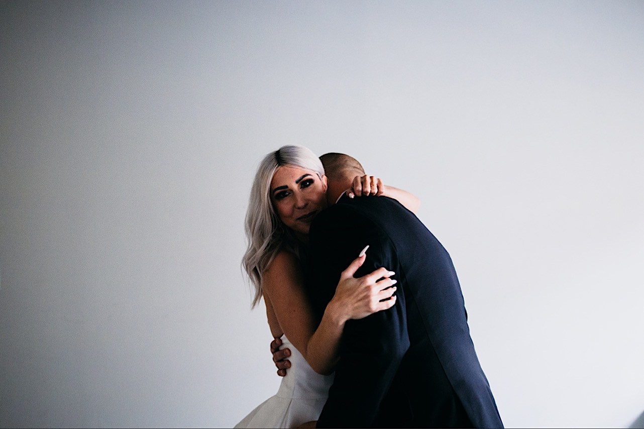 bride smiles while hugging her husband at their halloween elopement