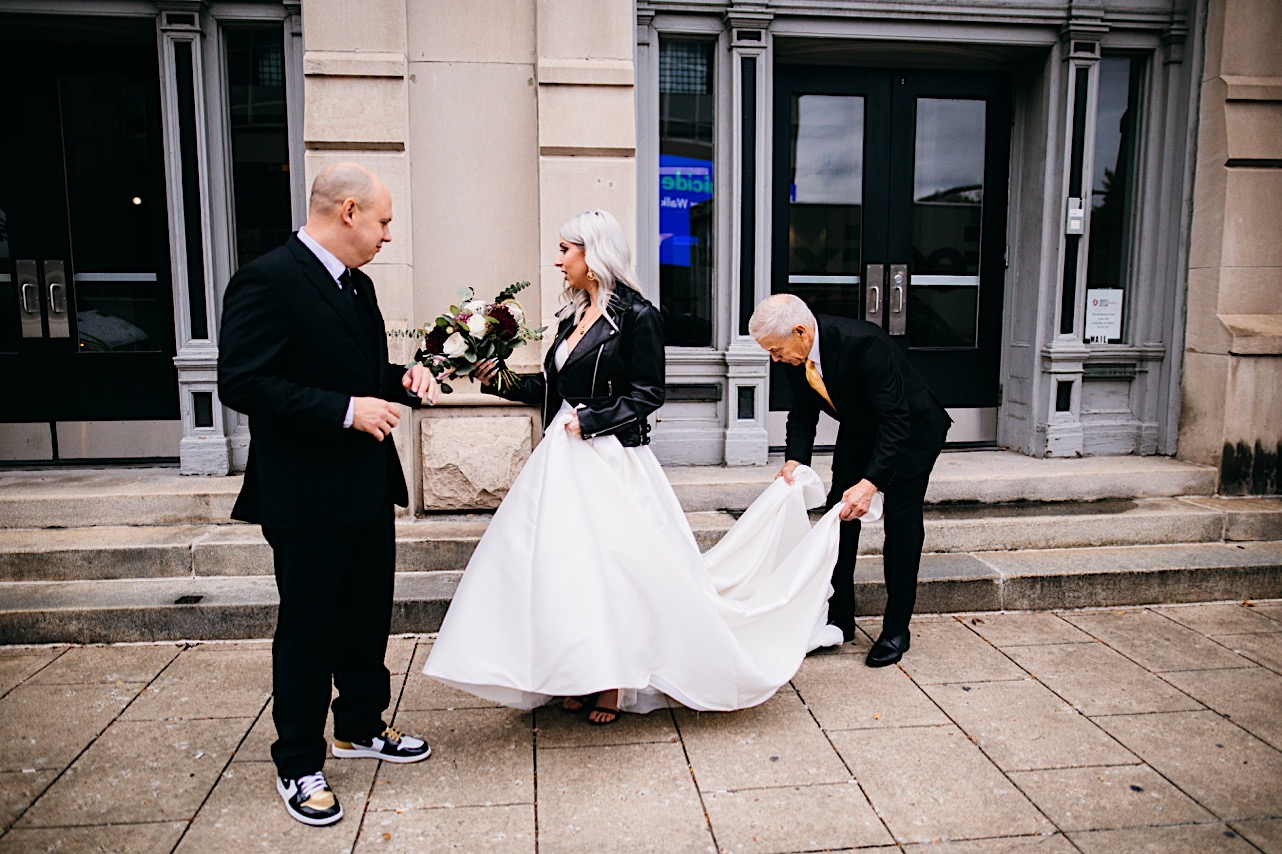bride is having her dress fixed as her and groom walk outside of the courthouse at thier halloween elopement