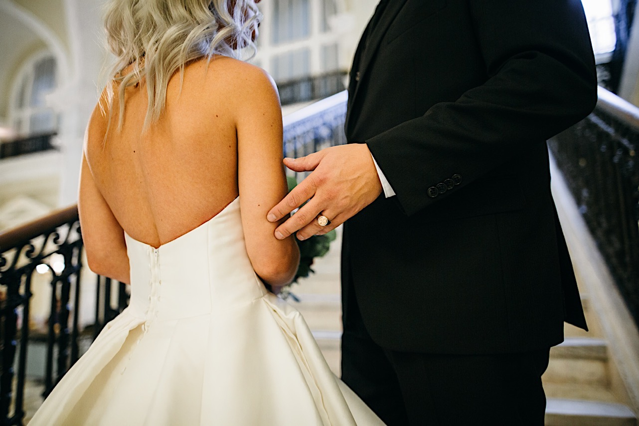 groom touches brides arm as they stand on the staircase at their halloween elopement