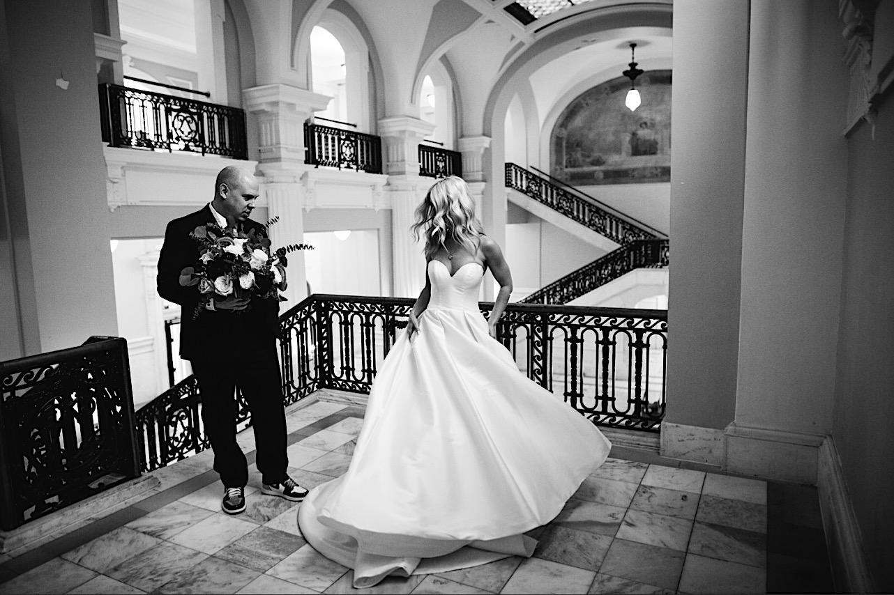 bride twirls in her wedding dress and looks at the husband in the courthouse at their halloween elopement