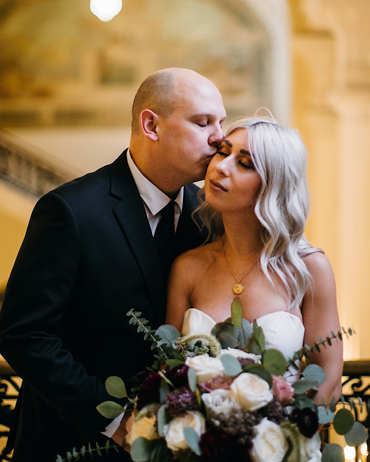 groom kisses bride on her cheek at the courthouse of their halloween elopement