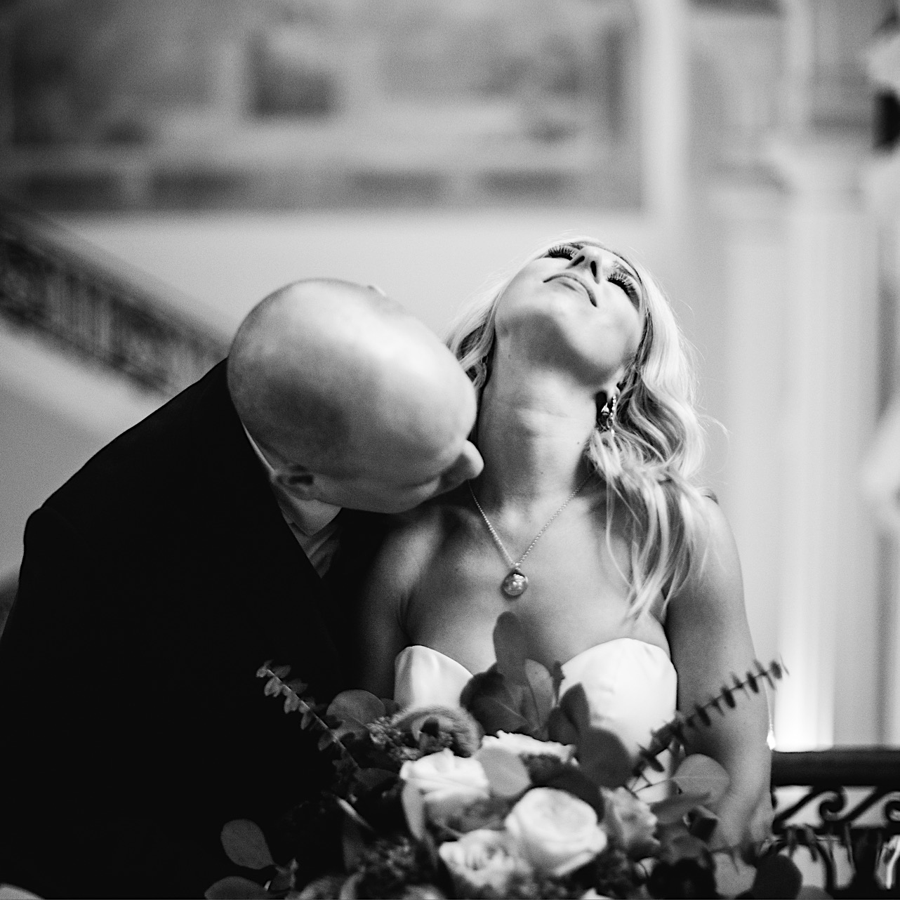 groom kisses bride on her neck at the courthouse of their halloween elopement