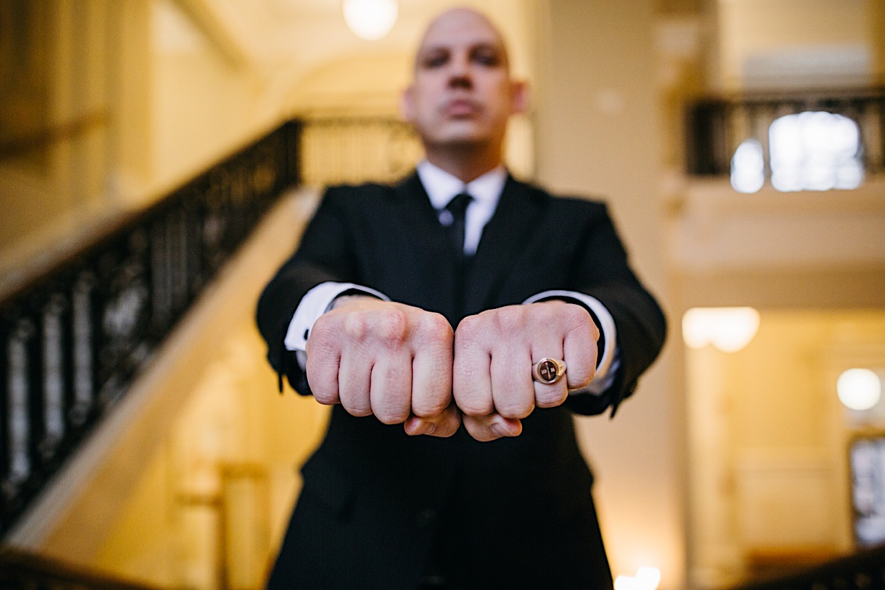 groom holds his knuckles together and shows his ring to the camera at his halloween elopement