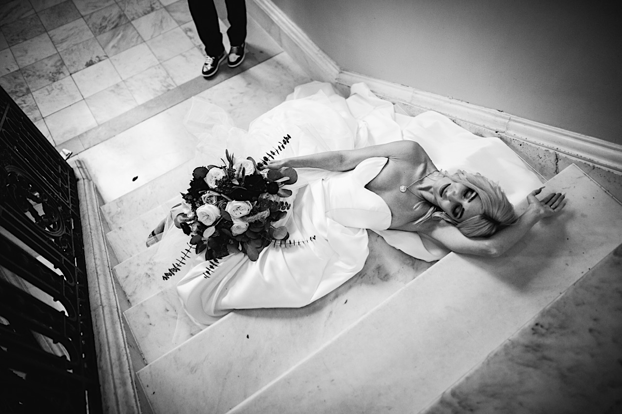 bride lays on the staircase at the courthouse of her halloween elopement
