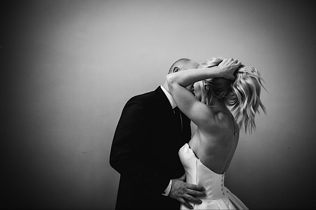 groom holds brides waist as she pulls her hair up at their halloween elopement