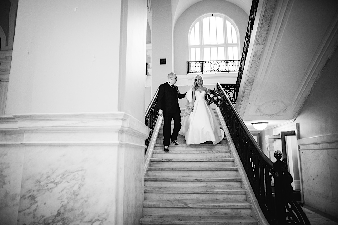groom holds the bottom of the brides dress as they walk down the stairs of the courthouse at their halloween elopement