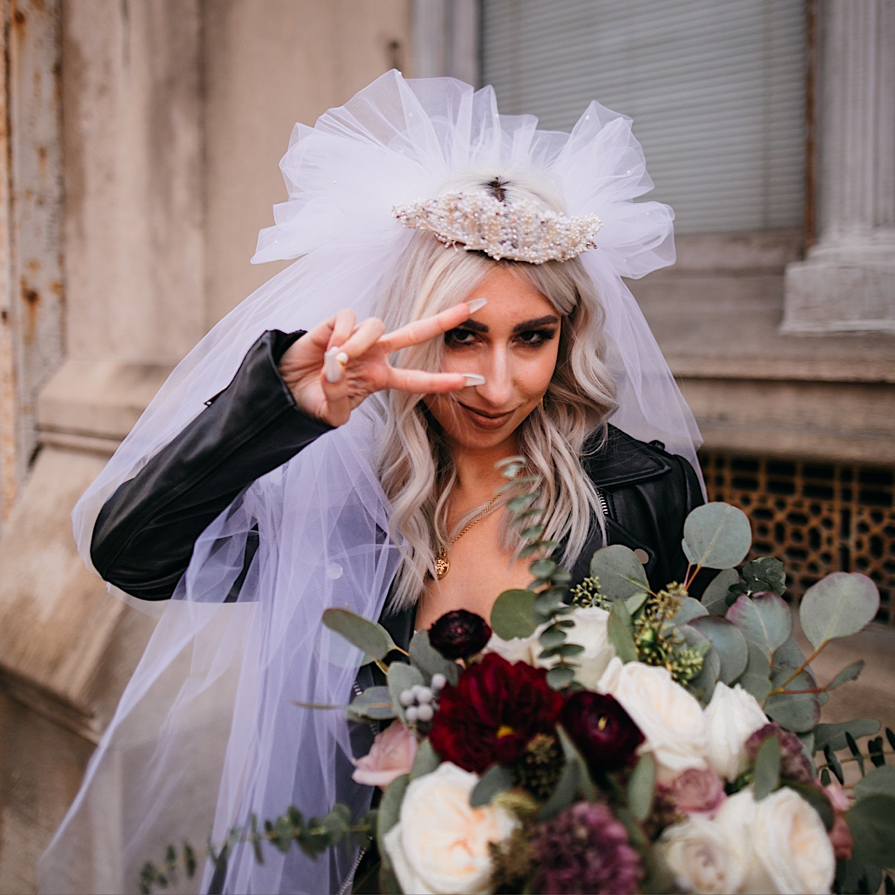 bride smiles and holds up a peace sign as she holds her bouquet and wears her veil at her halloween elopement