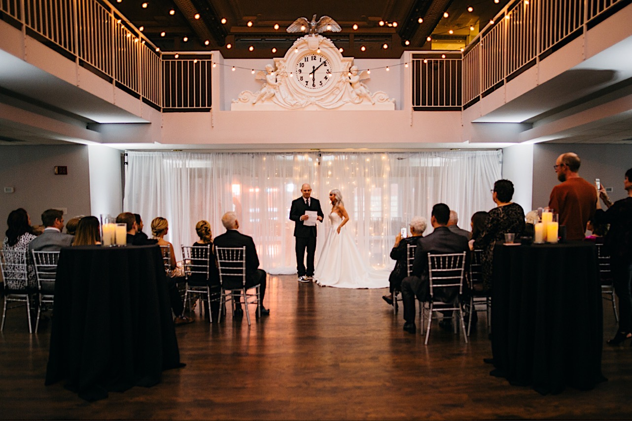 bride and groom stand at the front of the room in front of their family at their halloween elopement